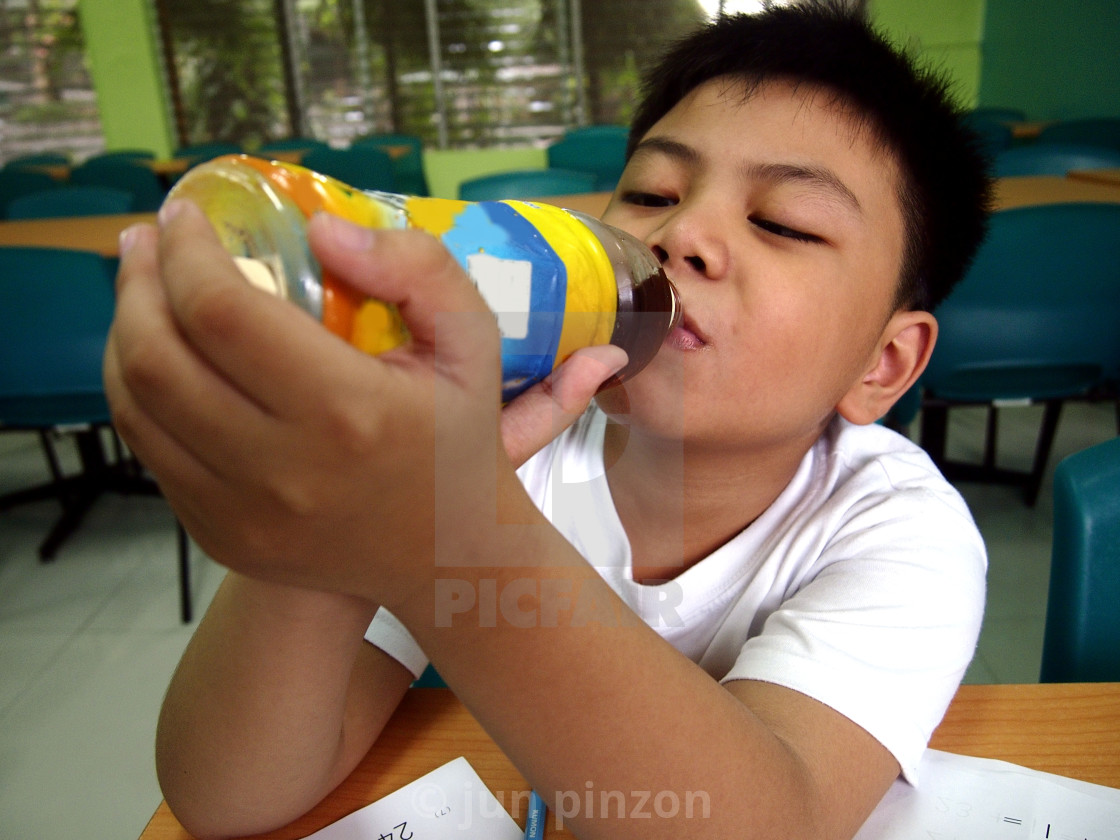 """""""Young kid drinking juice from a bottle"""" stock image"""