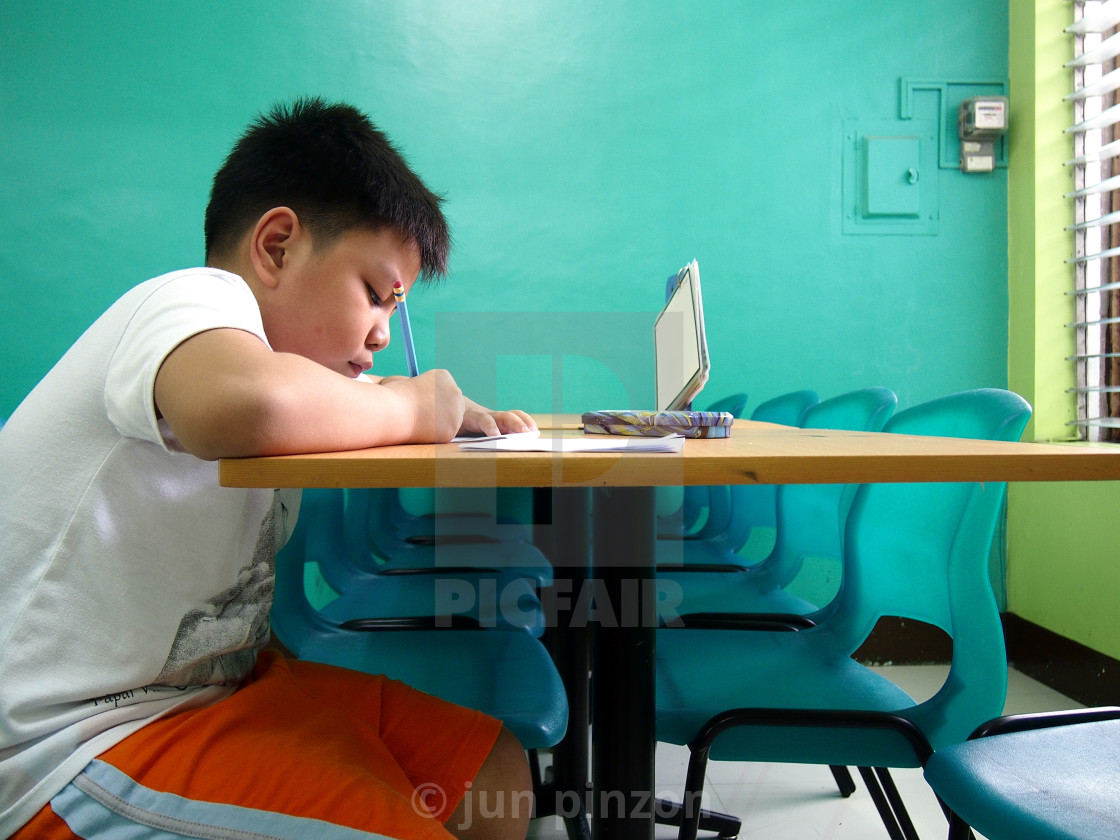 """""""Young kid writing on a table"""" stock image"""