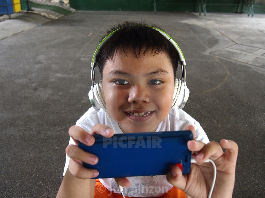 """""""Young kid with a smartphone and headphones"""" stock image"""