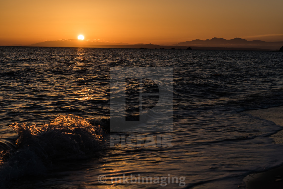 """Sunrise and breaking waves"" stock image"