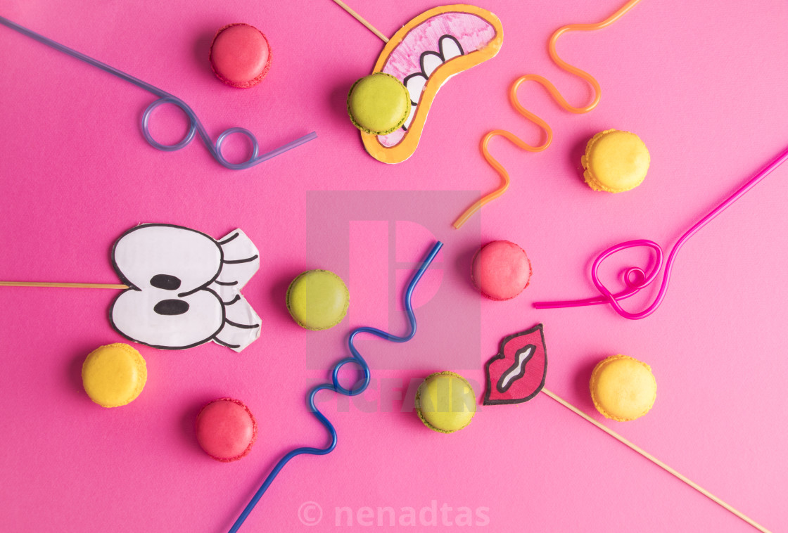 """Macaroonas with party accessories on pink background"" stock image"