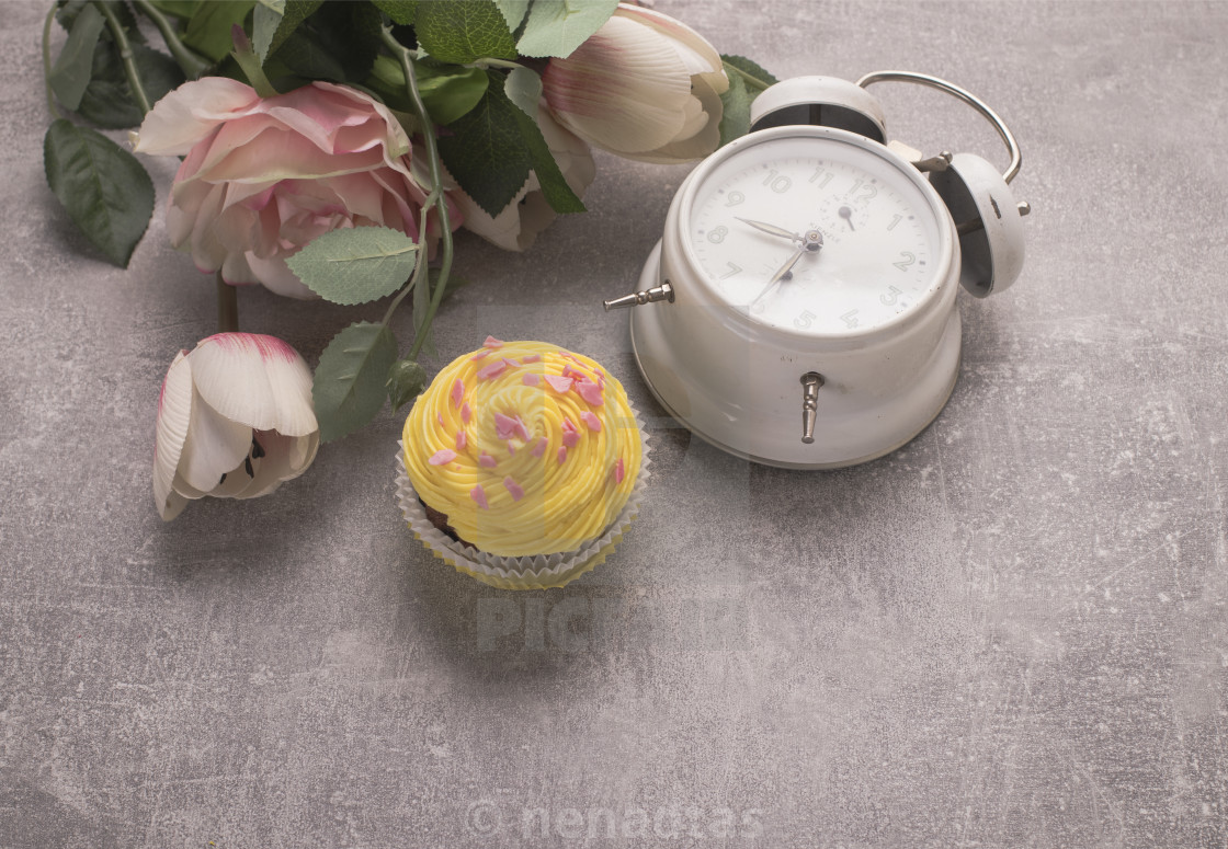 """Muffin whith flowers and clock on grey background on top view"" stock image"