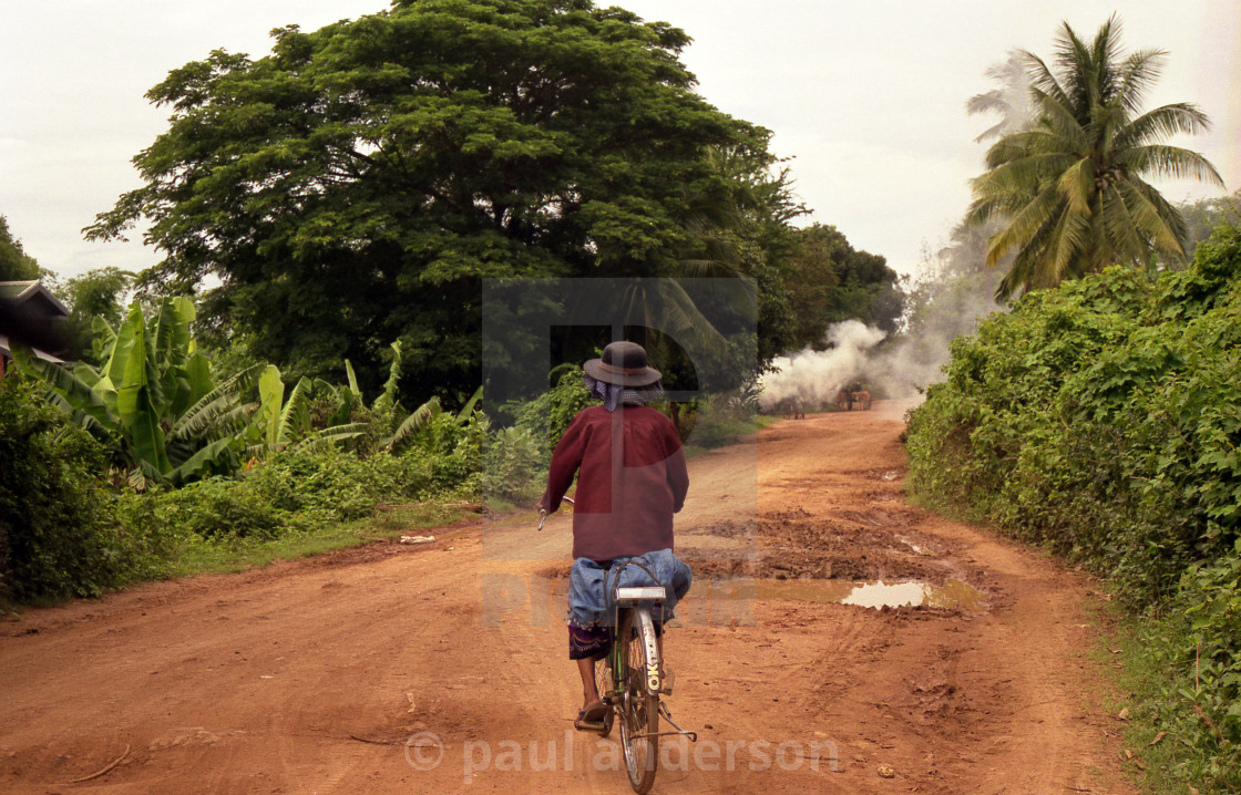 """A cyclist on a road in Laos"" stock image"