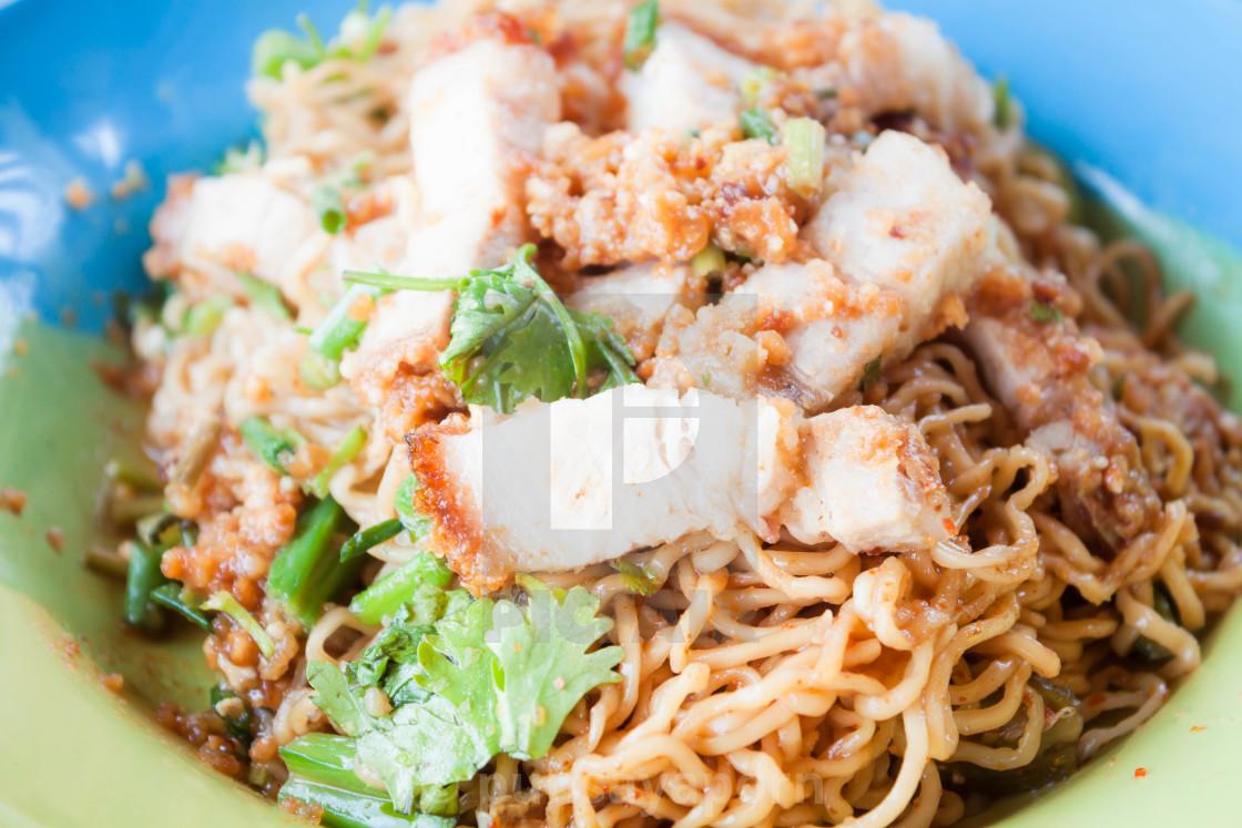 Close up crispy pork on stir fried spicy noodles - License