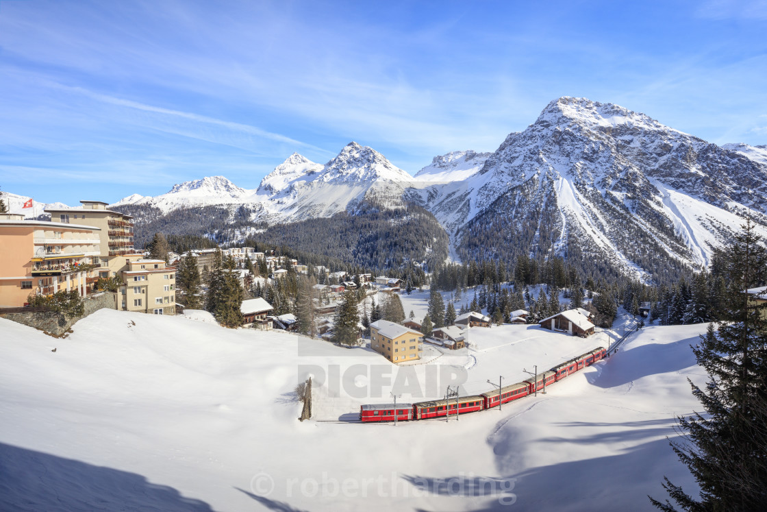 """Red train of Rhaetian Railway passes in the snowy landscape of Arosa,..."" stock image"