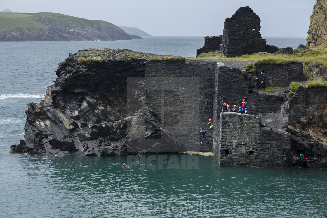 """Coasteering activity with people jumping from the former quarry building at..."" stock image"