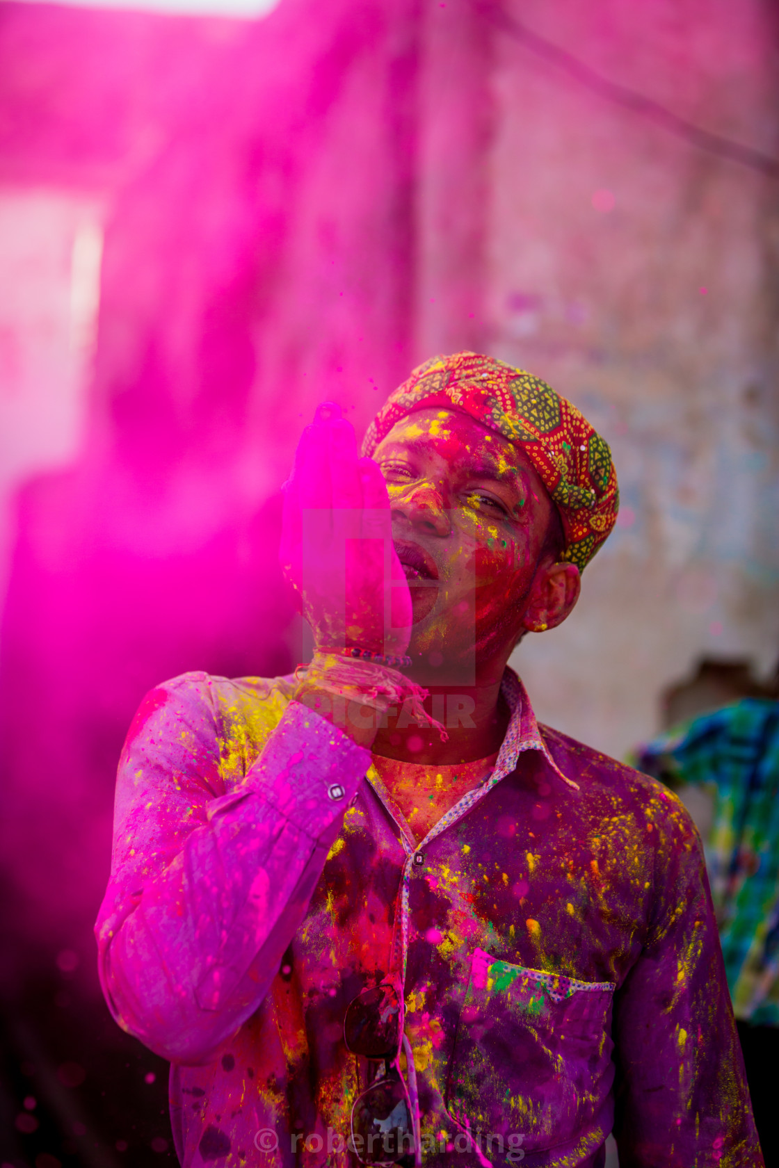 """Man throwing colored pigment, Holi Festival, Vrindavan, India"" stock image"
