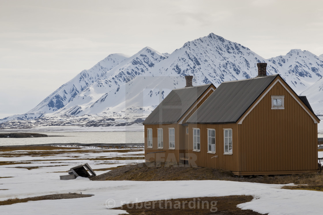 """Wooden buildings with snowy mountains behind, Ny Alesund, Spitsbergen..."" stock image"