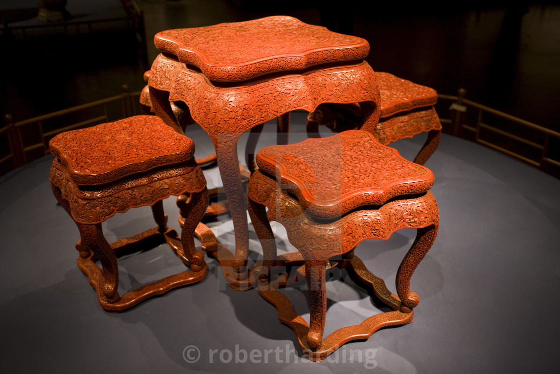 """Red lacquer square table and stools with carved floral design on display in..."" stock image"