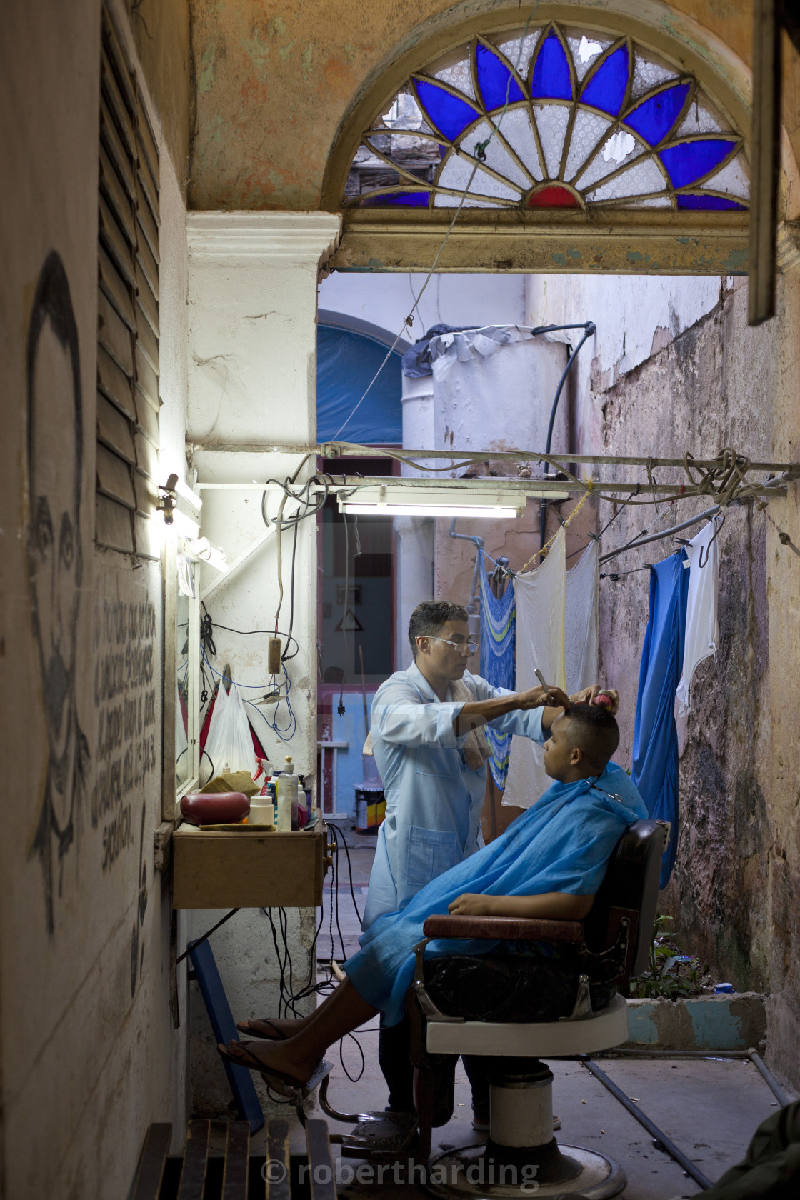 """Man having haircut in backstreet barber shop, Havana Viejo, Havana, Cuba,..."" stock image"