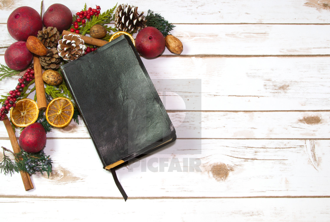 An Old Rustic Bible with Christmas Garland Potpourri on a wood p ...