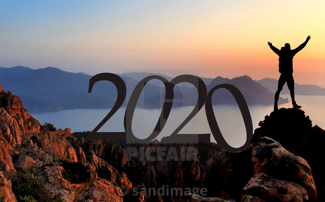 """2020 number and a silhouette of hiker enjoying at the top of cliff overlooking the sea at sunset"" stock image"