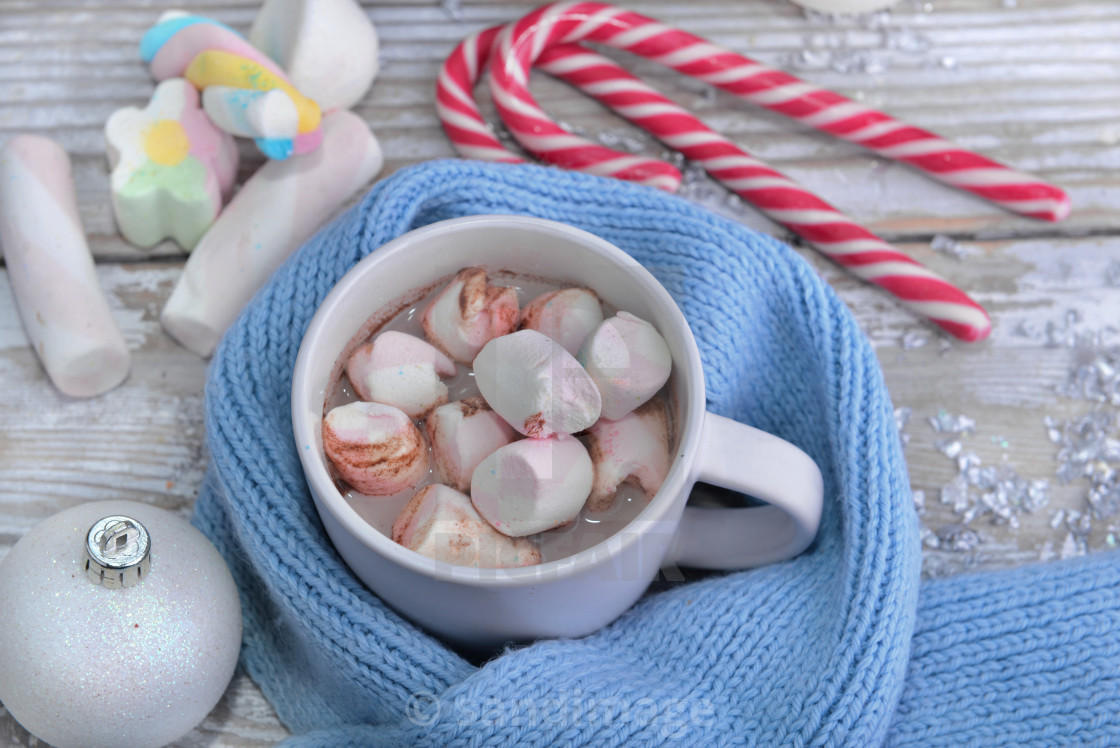 """mug full of marshmallow in milk chocolate on a blue child scarf and candy canes"" stock image"