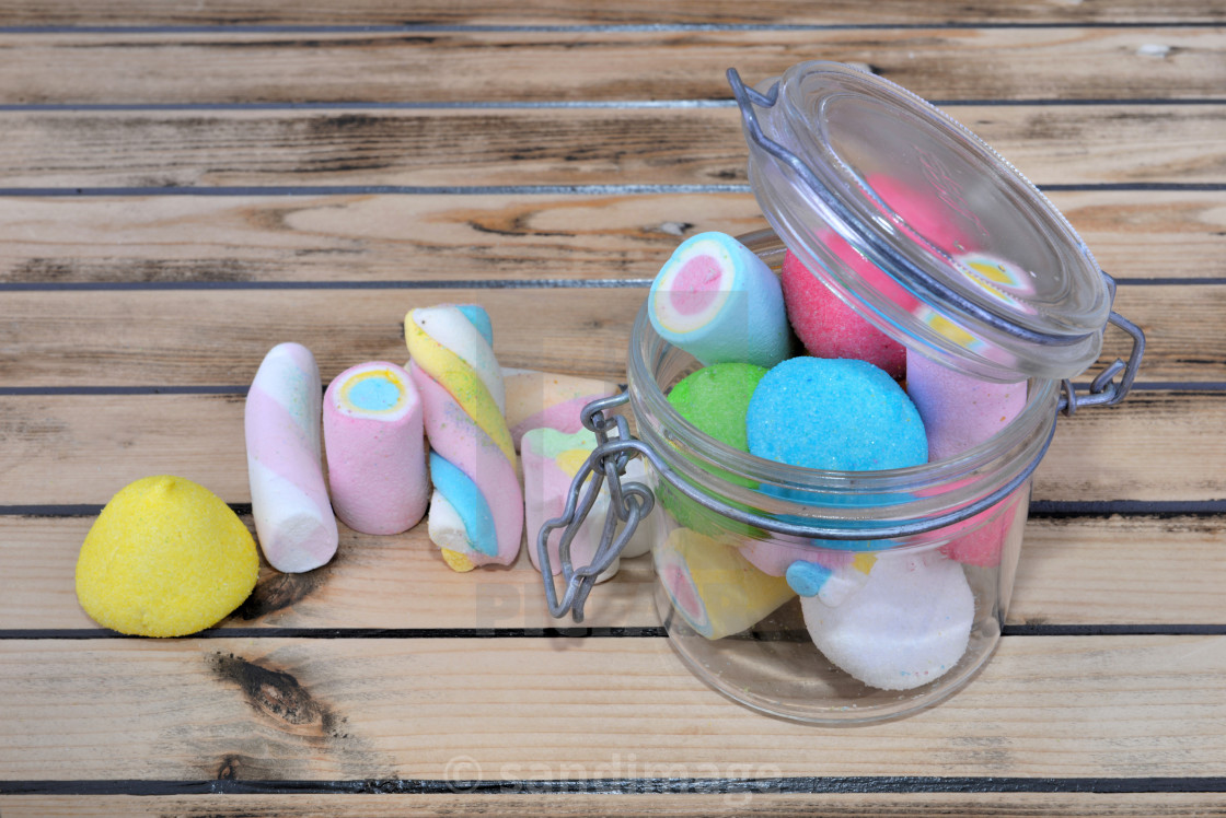 """colorful marshmallows in a glass jar on a wooden background"" stock image"