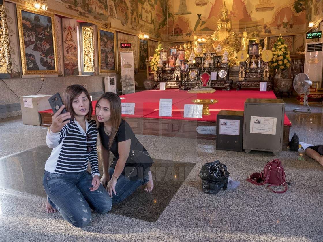 """""""Two girls taking selfie on smartphone in the temple at bangkok thailand..."""" stock image"""