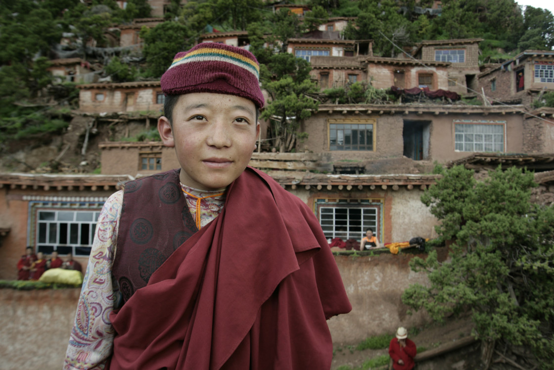 """""""Nun in front of earthen homes, Dechenling Nunnery, Tibet"""" stock image"""