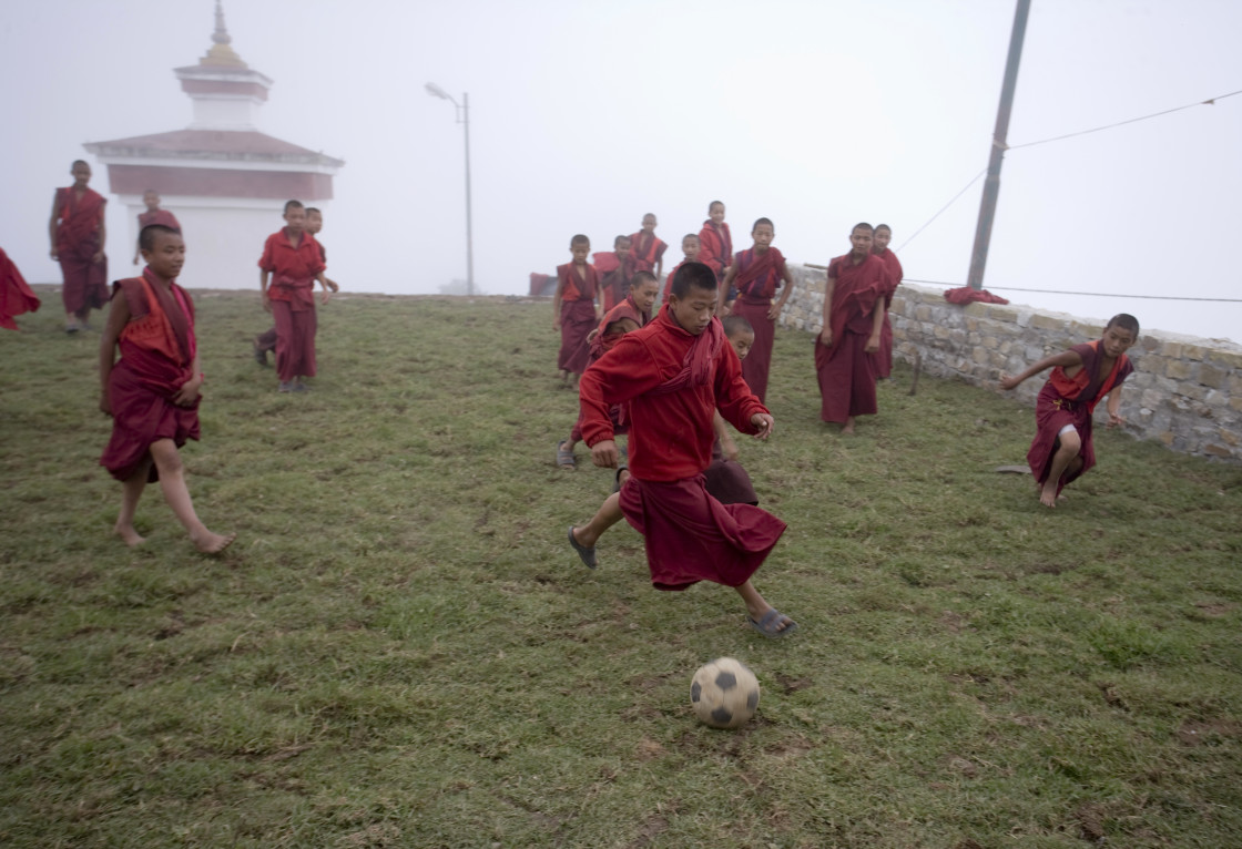 """Monks playing soccer, Dungsum Yongla, Bhutan"" stock image"