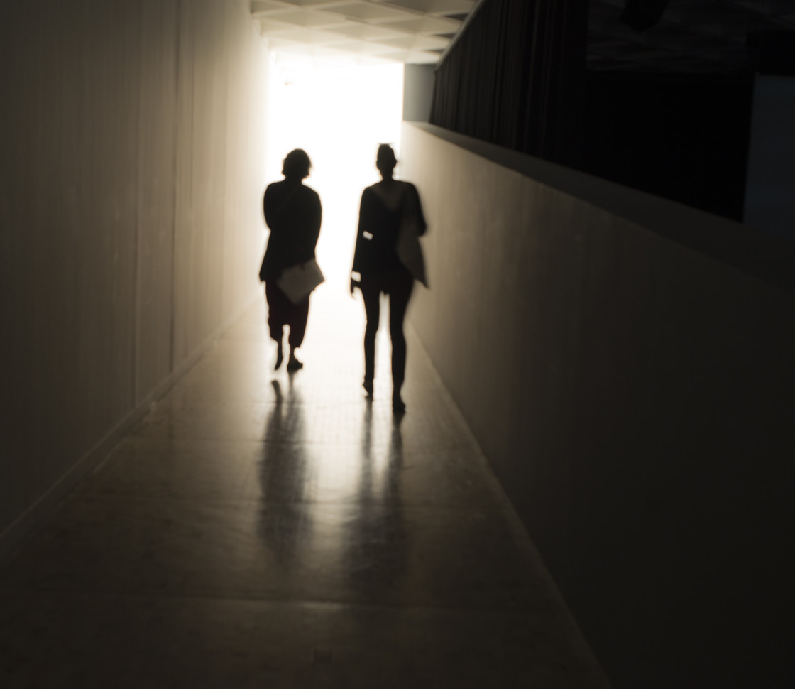 """Two friends walking towards the light"" stock image"