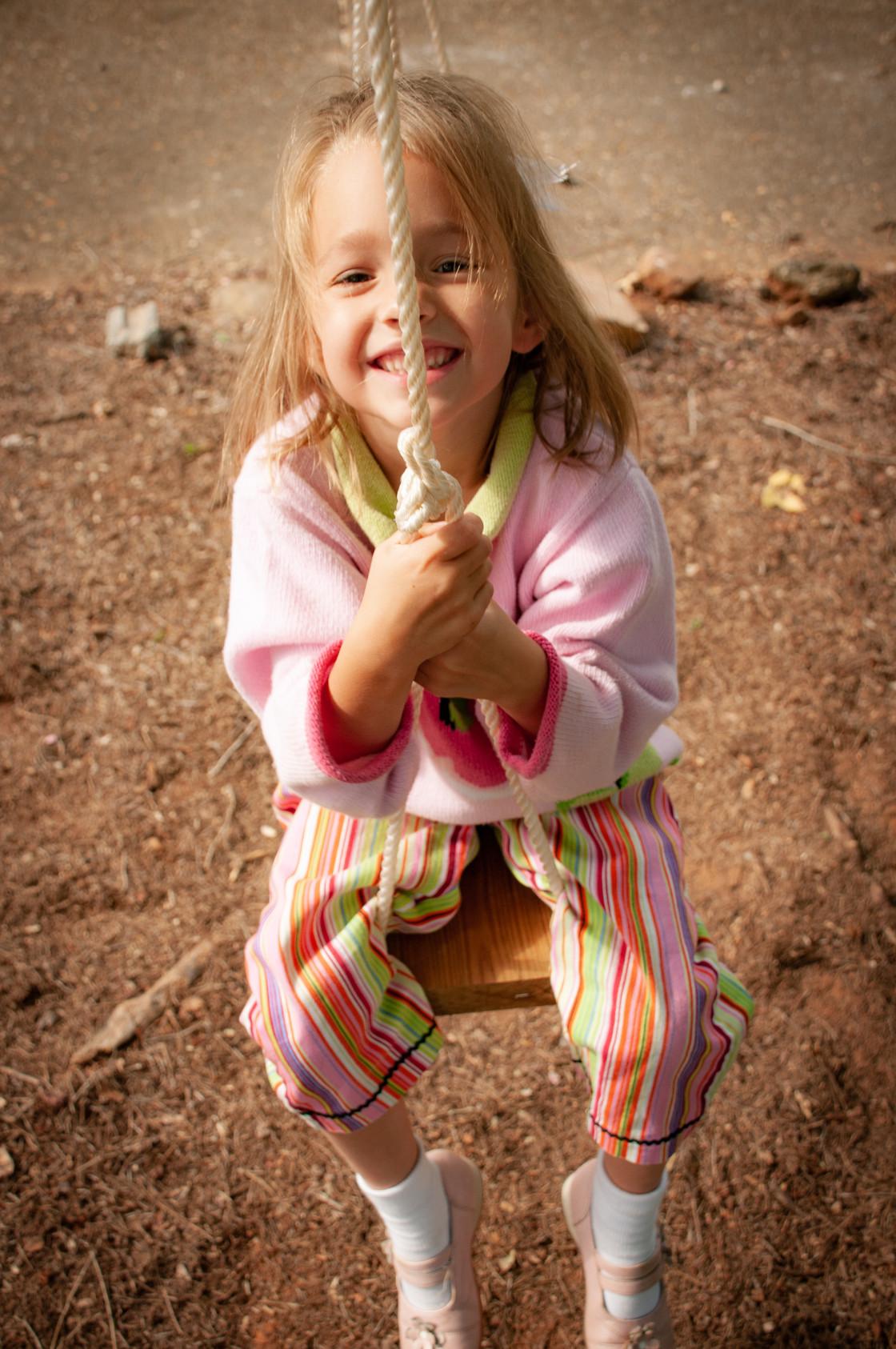 """Girl Swinging on Swing - Playful"" stock image"