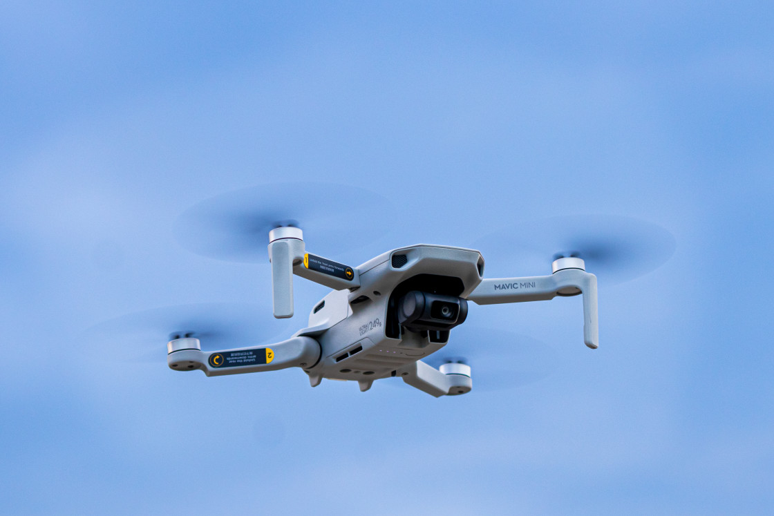 """Small camera drone flying at cloudy sunset"" stock image"
