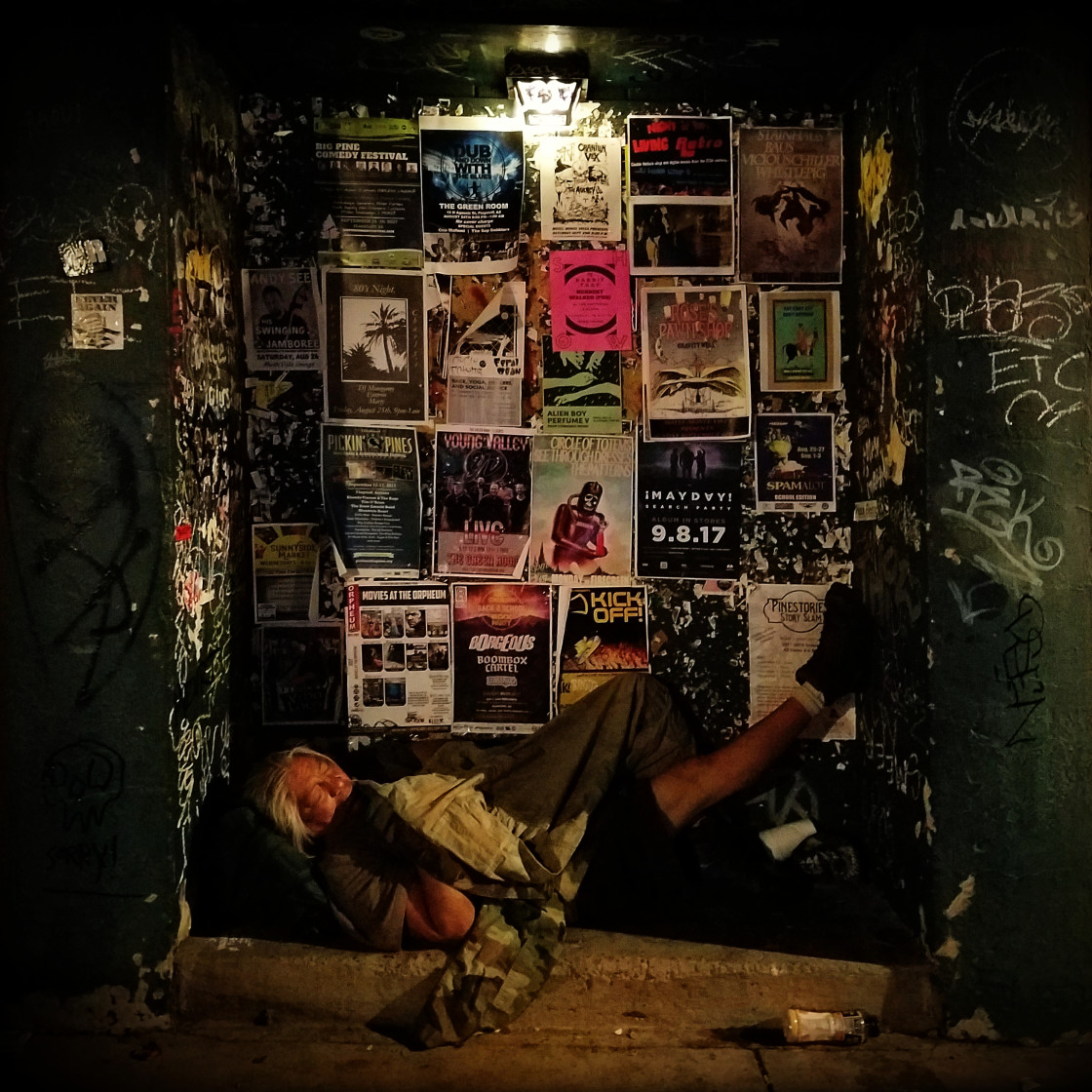 """A homeless man sleeps on the streets in an alcove amidst band flyers and graffiti."" stock image"