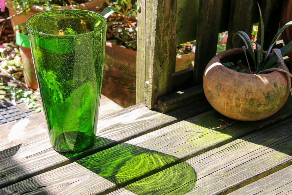 """A GREEN ANTIQUE VASE WAITS IN THE GARDEN"" stock image"