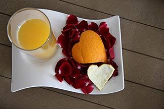 Orangenherz und Rosenblütenblättern auf Tablett