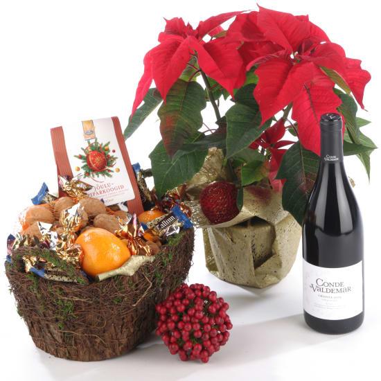 Weihnachtsstern mit Korb voller Süssigkeiten und Rotwein