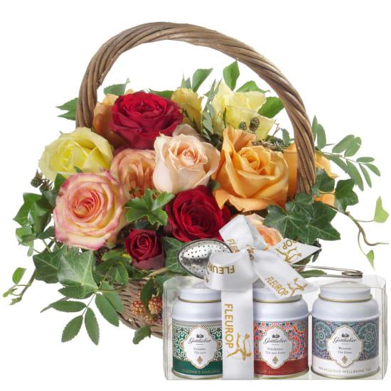 Une corbeille remplie de roses avec coffret cadeau de thés Gottlieber