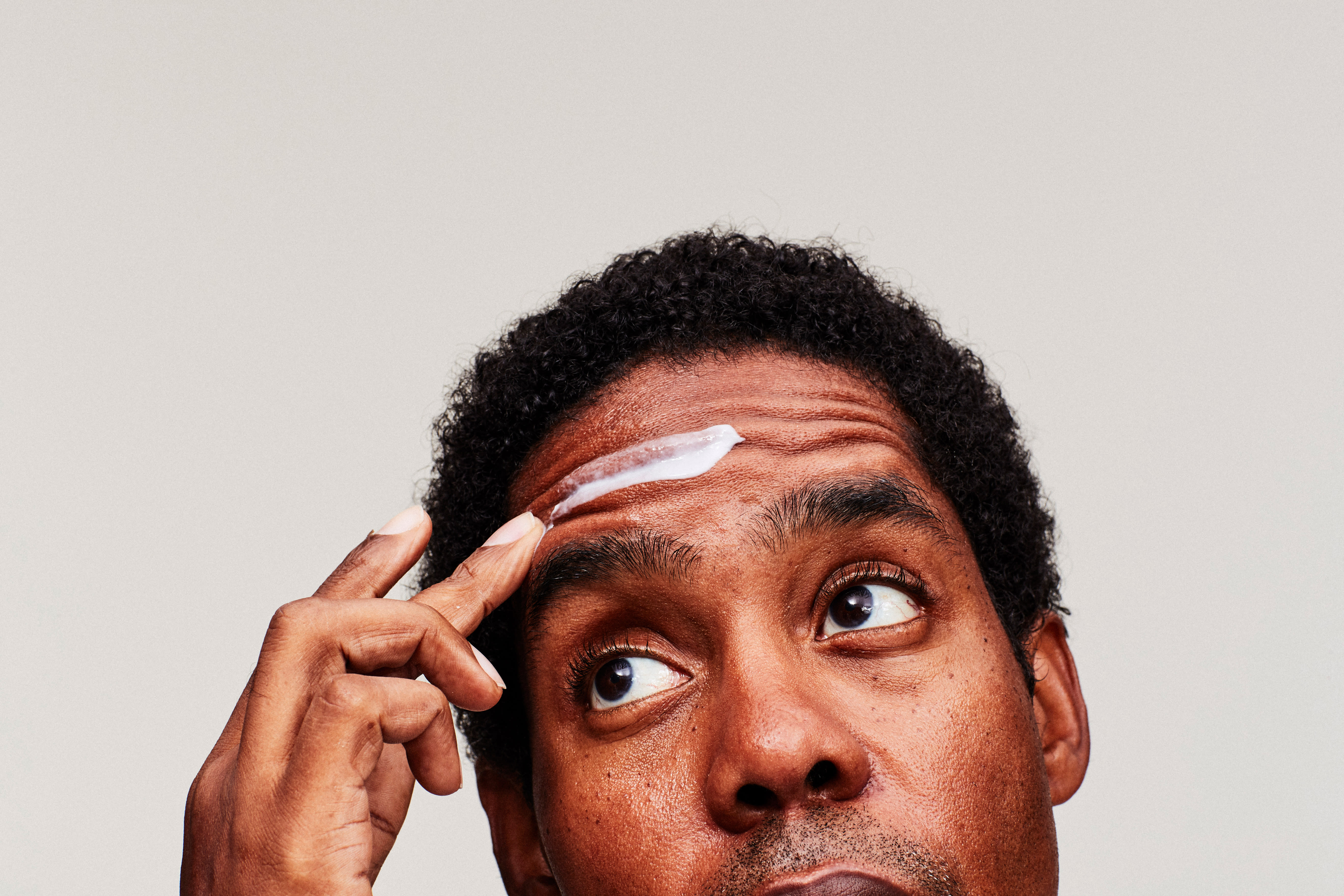 A closeup of a man putting cream on his forehead