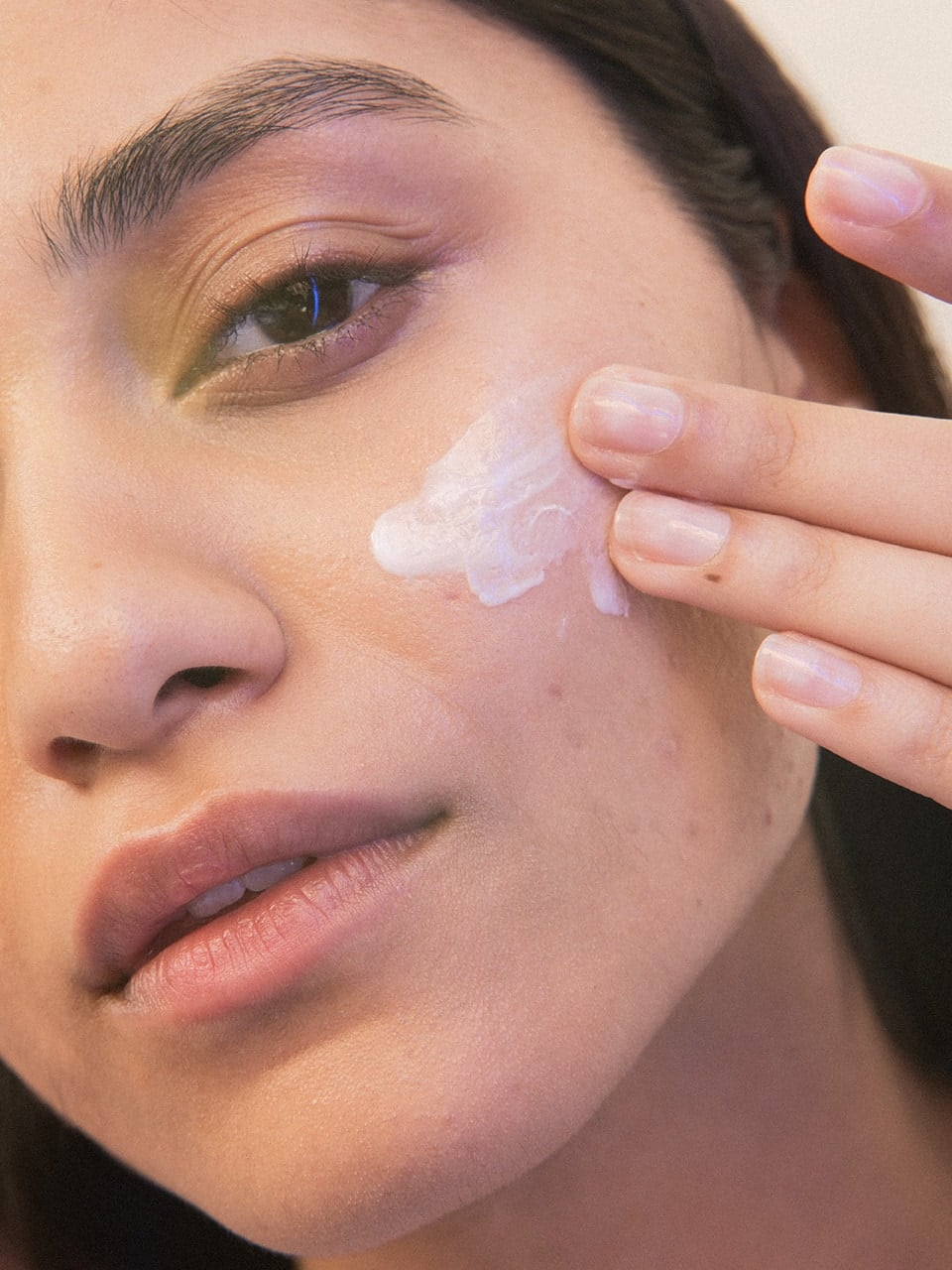 a woman rubbing in facial acne cream