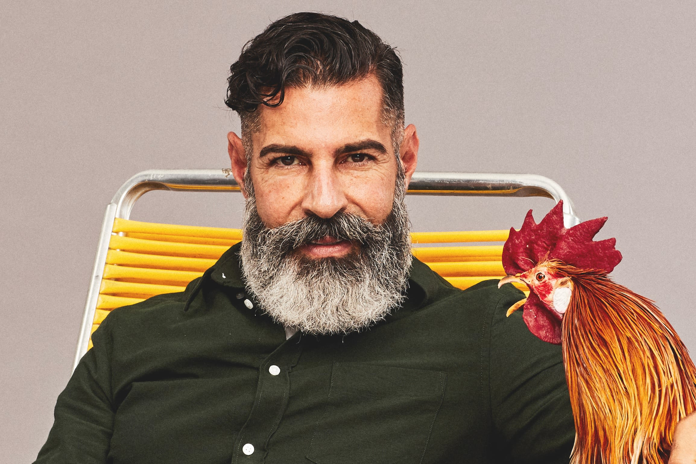 A bearded man seated holding a rooster.