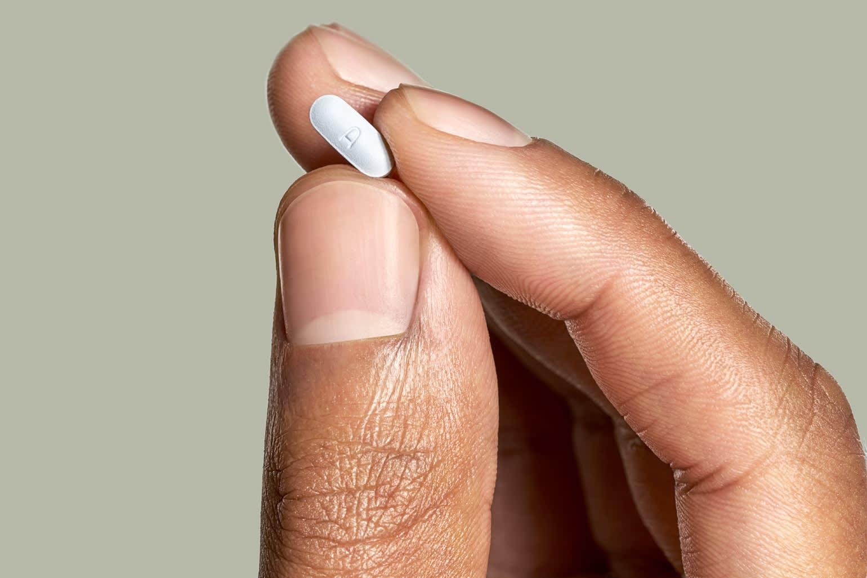 A hand holding a Hims Sertraline pill