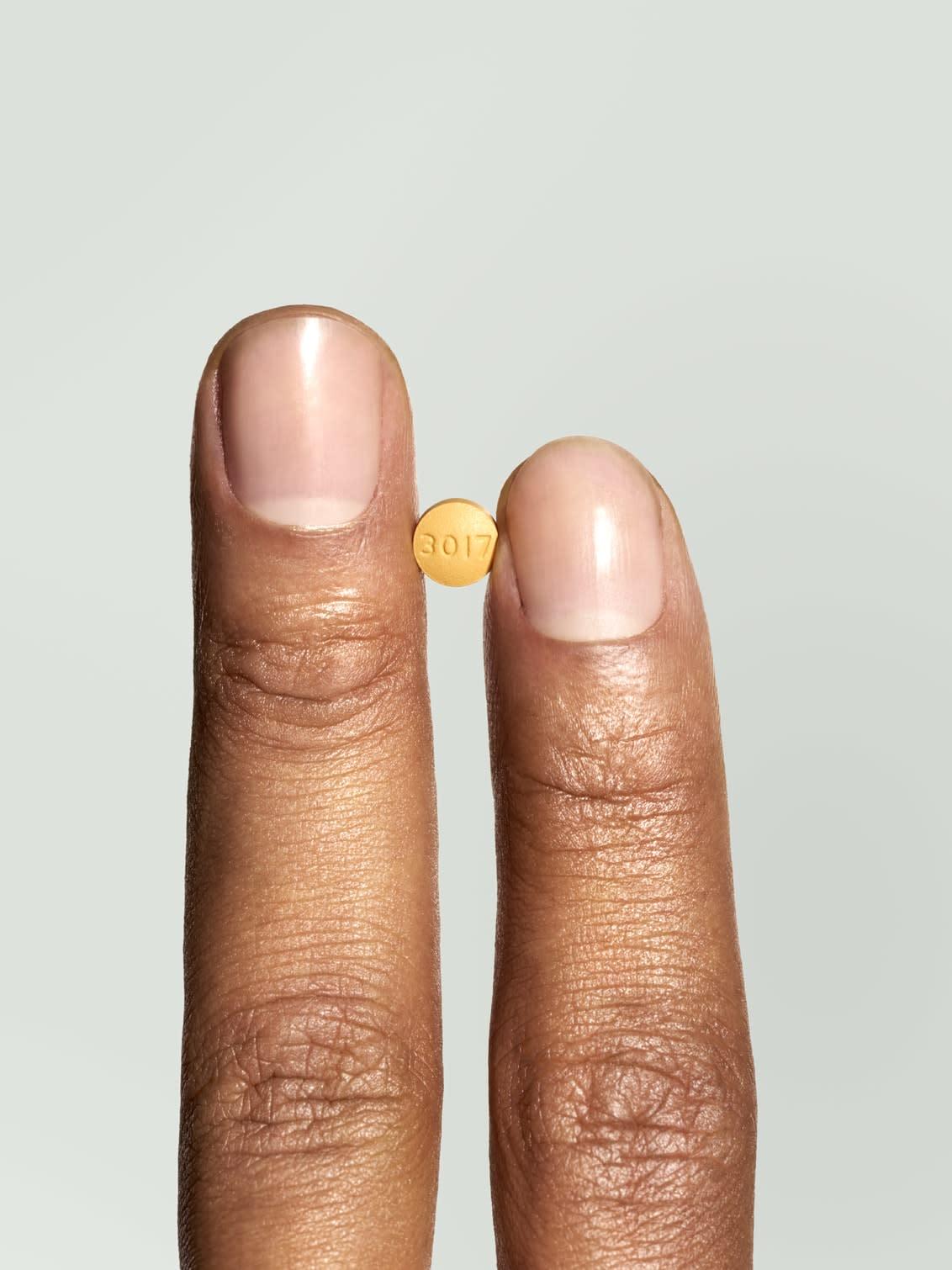 A hand holding a Hims Tadalafil pill