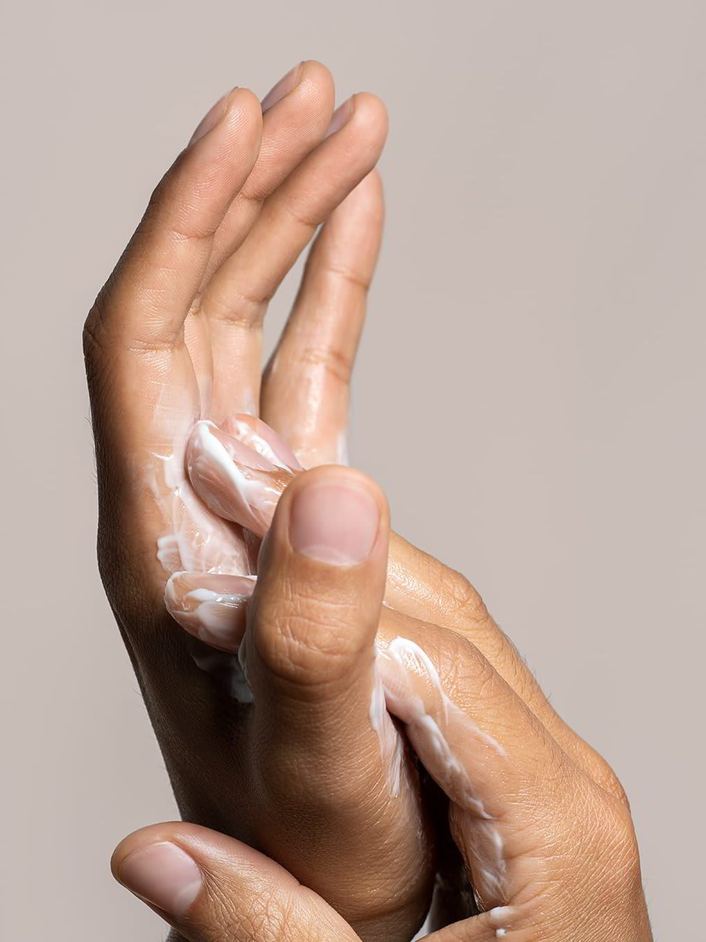 A closeup of a man applying cream to his hands