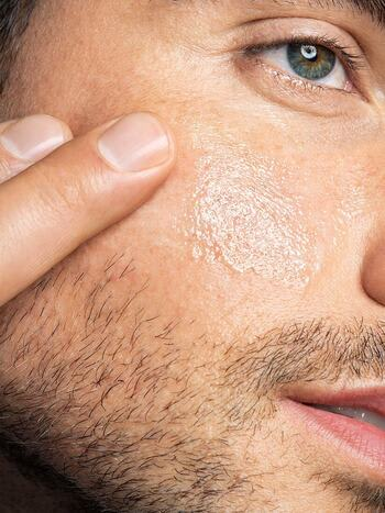 A closeup of a man touching his face