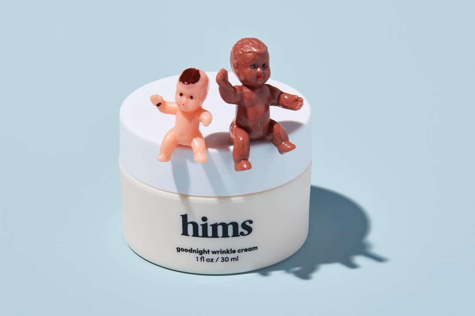 Two baby figurines sitting on top of a container of Hims goodnight wrinkle cream