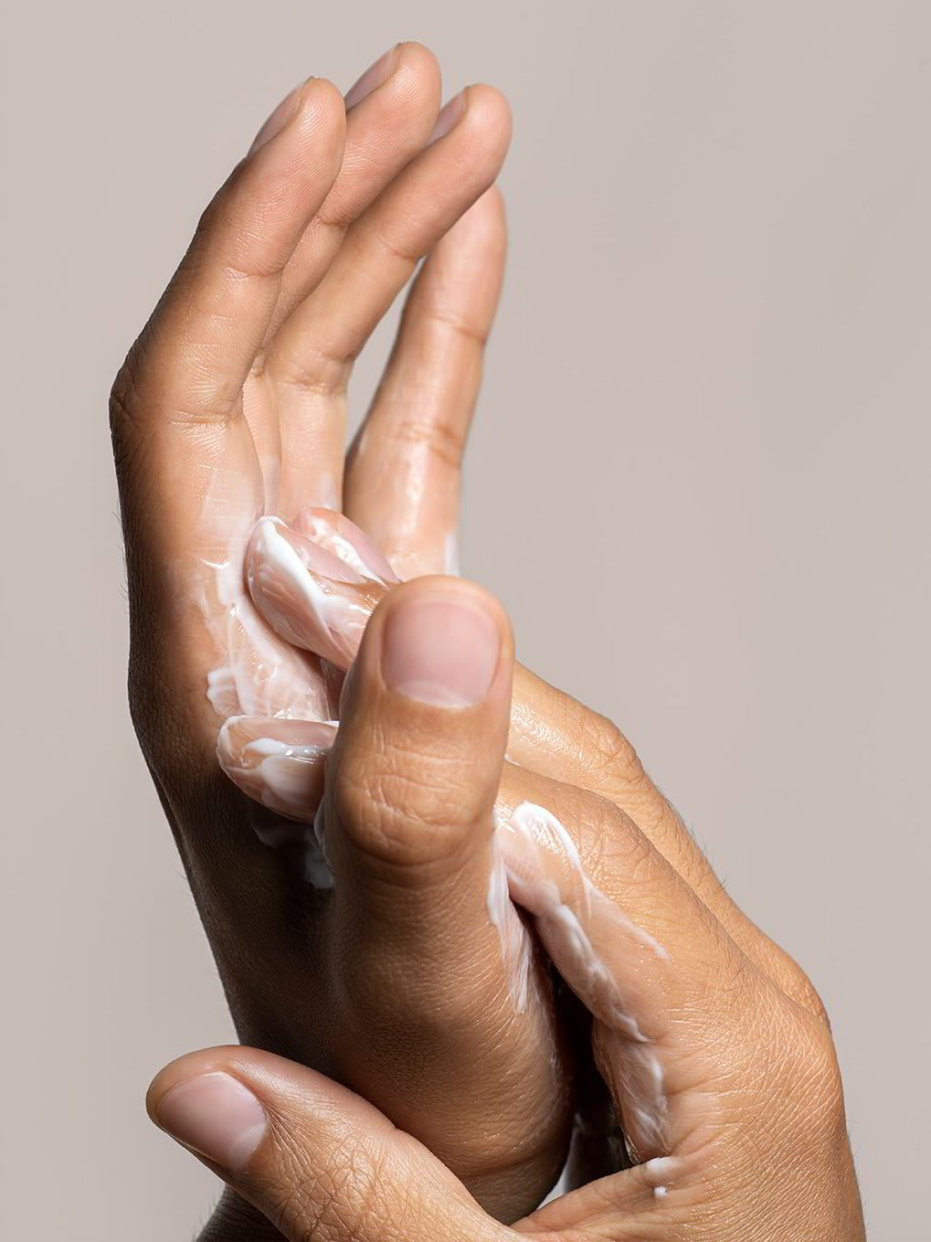 A closeup of a young man applying skin care product to his hands