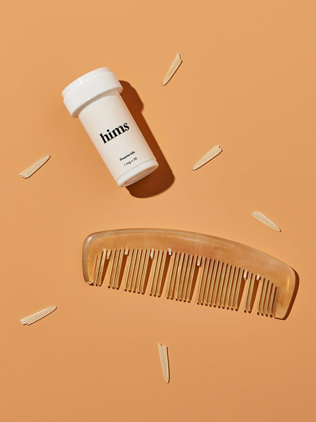 A pill bottle and a comb with its teeth falling out