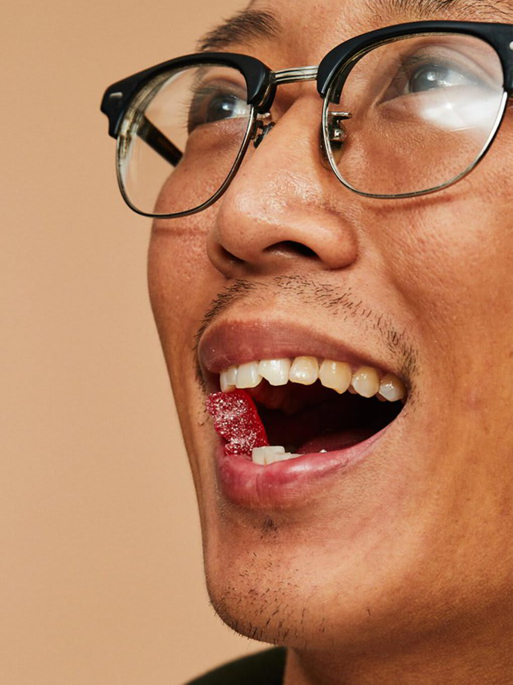 A man with a red gummy between his teeth