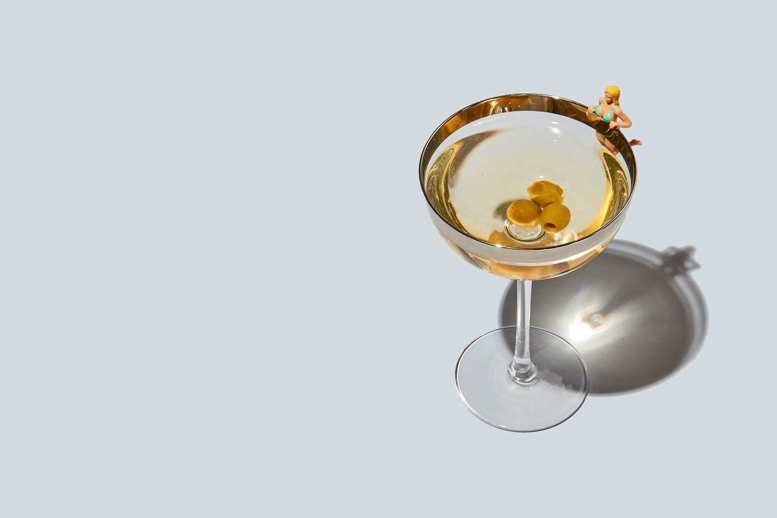 A small female figurine hangs off the edge of a cocktail glass