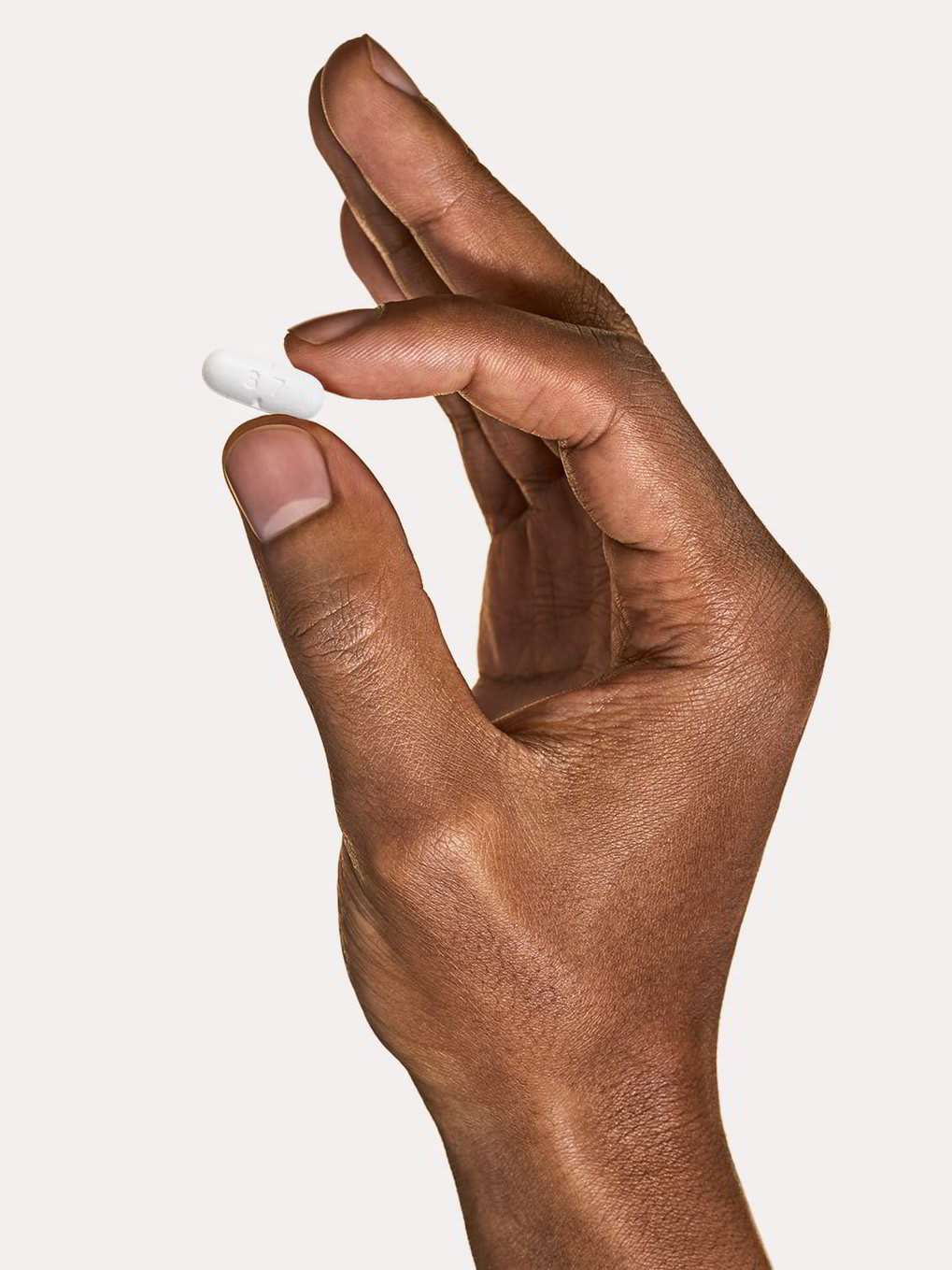 A hand holding a generic valtrex pill