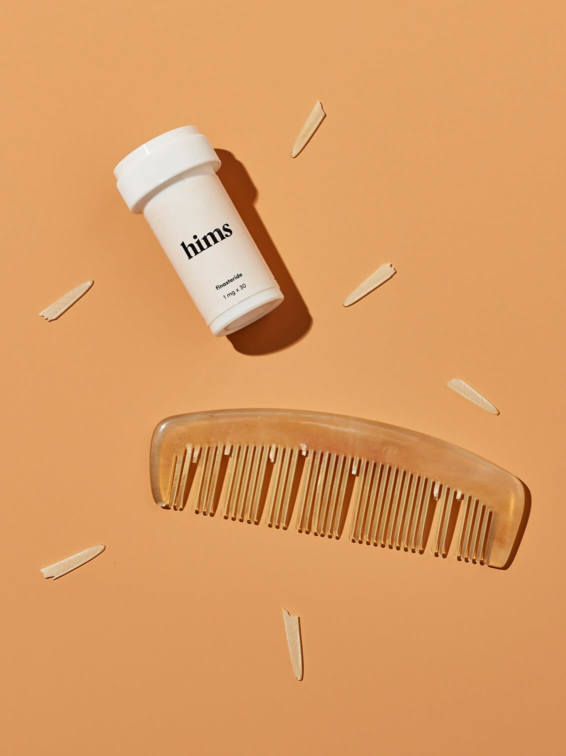 A bottle of Finasteride and a comb with its teeth falling out, scattered around