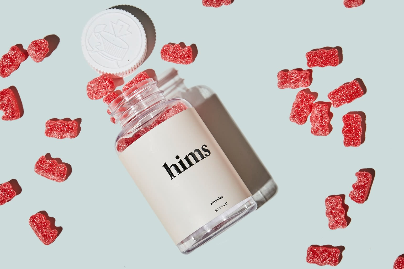 A bottle of red gummies on its side with the lid off and gummies spread around it