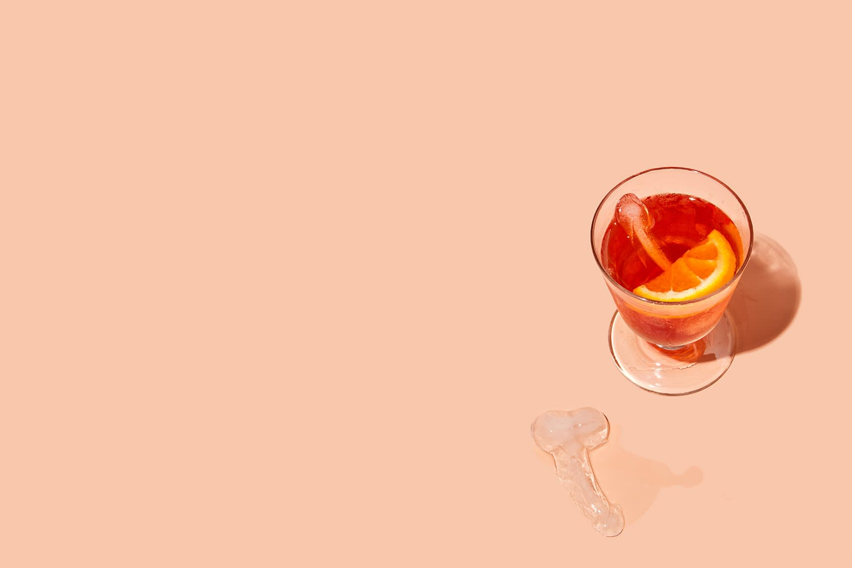 A red drink with a lemon slice in a glass