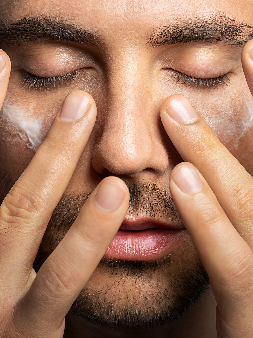 A closeup of a man applying skin care product to his face