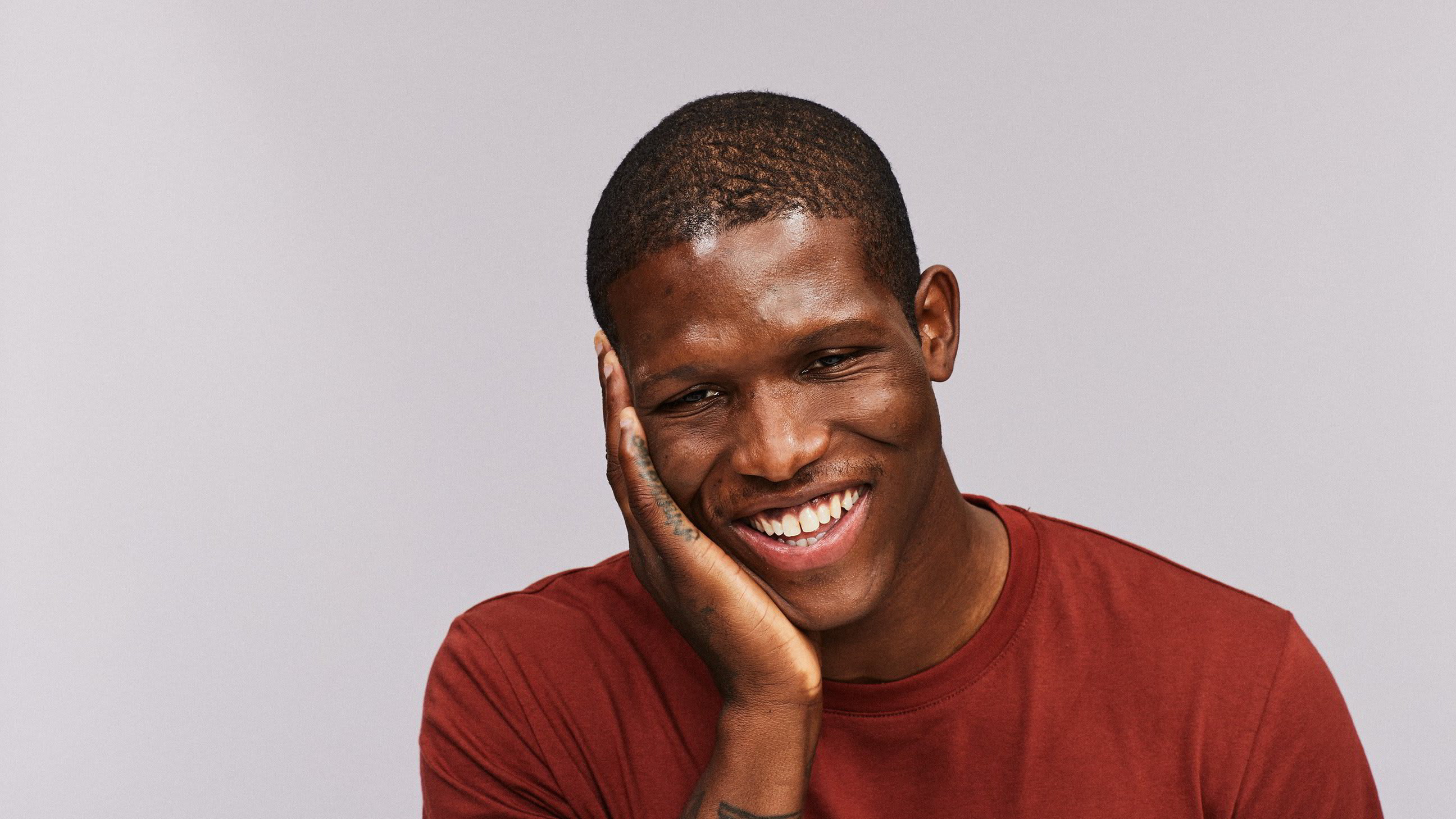 A young man smiling in disbelief at his smooth skin