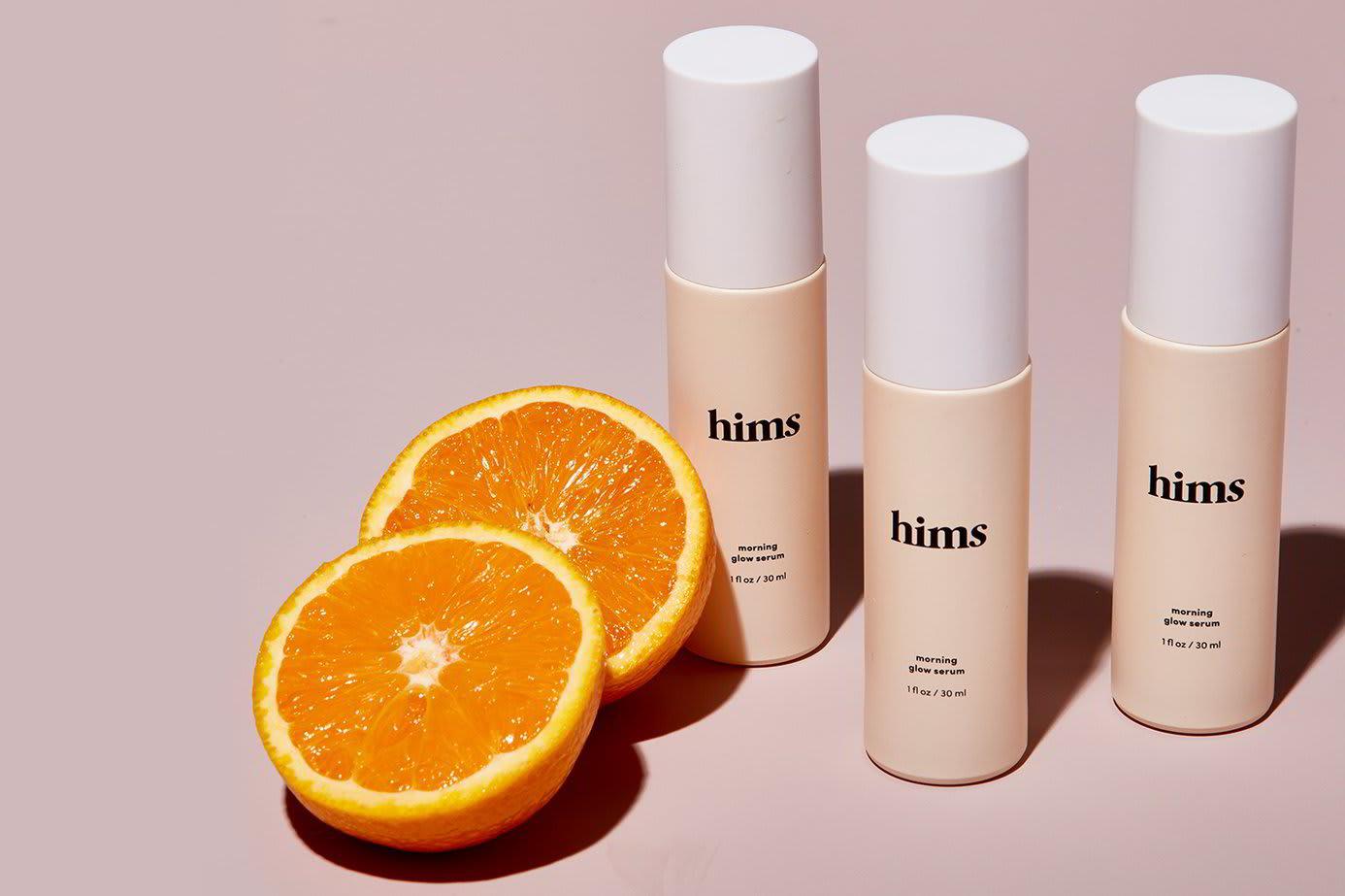 Many bottles of Hims Vitamin C Serum, accompanied by orange slices
