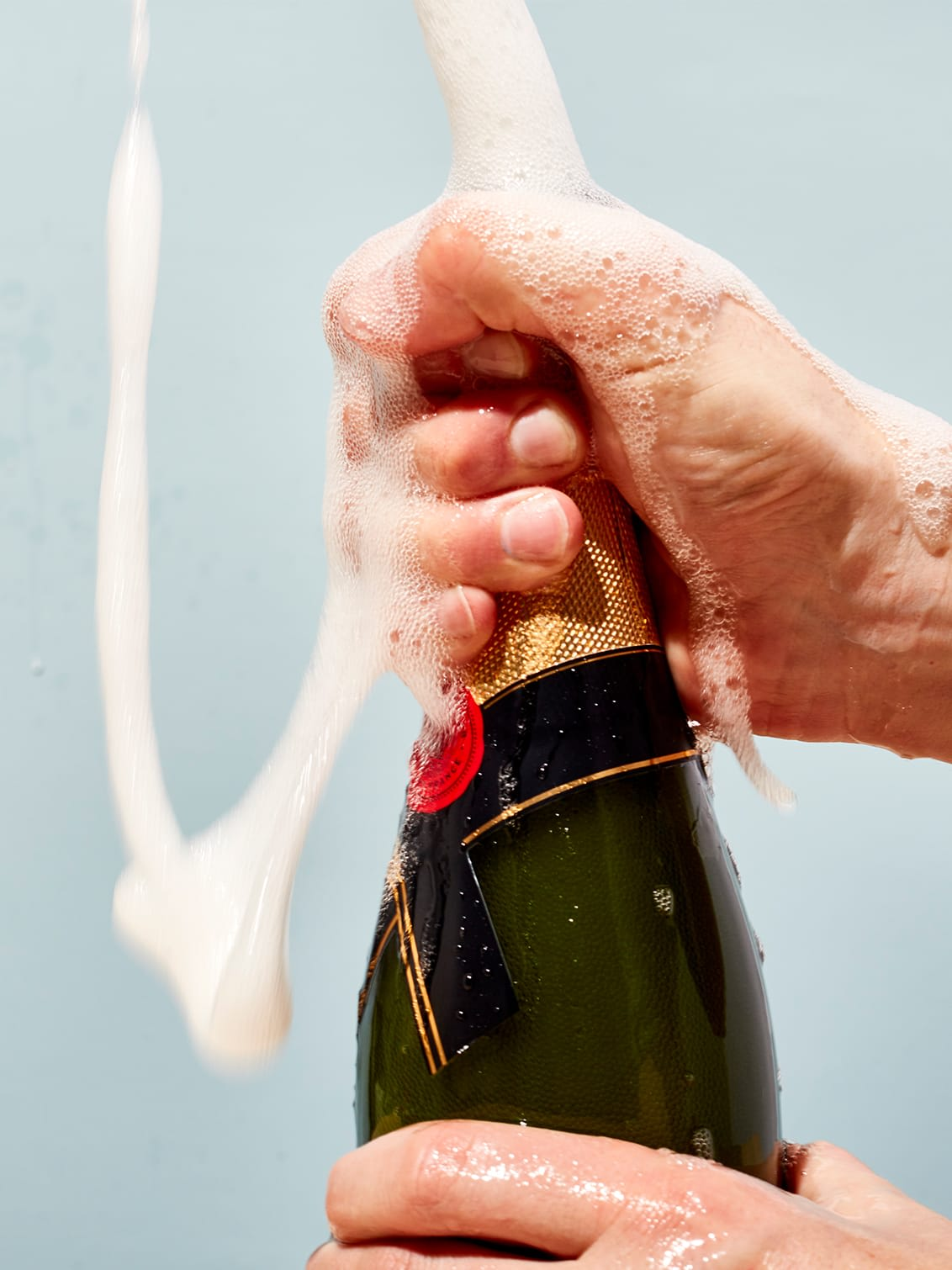 A bottle of champagne suggestively popped by a hand