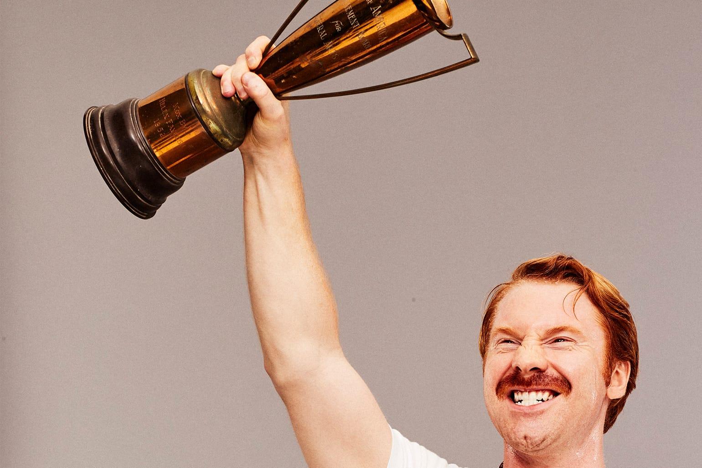 A triumphant man holding a trophy